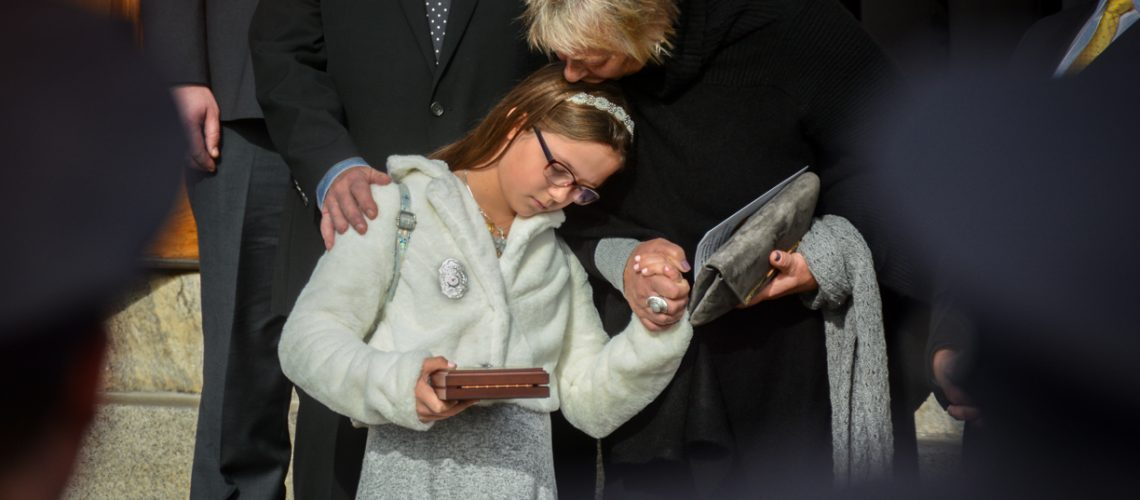 The 9 year-old daughter of Worcester Firefighter Christopher Roy receives some comfort and support from her grandparents as her father's casket is placed onto Engine 5. Ava is holding the Martin E. Pierce Medal of Honor that she received during the funeral service. The award is given to the families of firefighters killed in the line of duty across the country but is named after Martin Pierce who was a Boston firefighter.